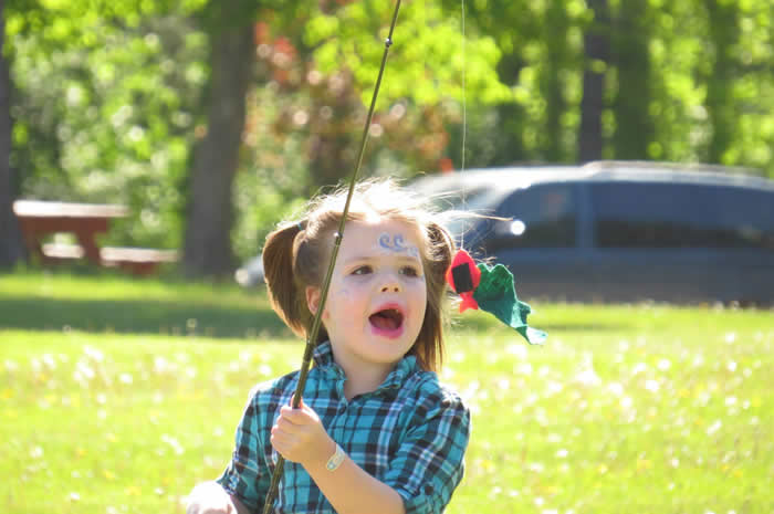 A young girl playing with a fishing pole.