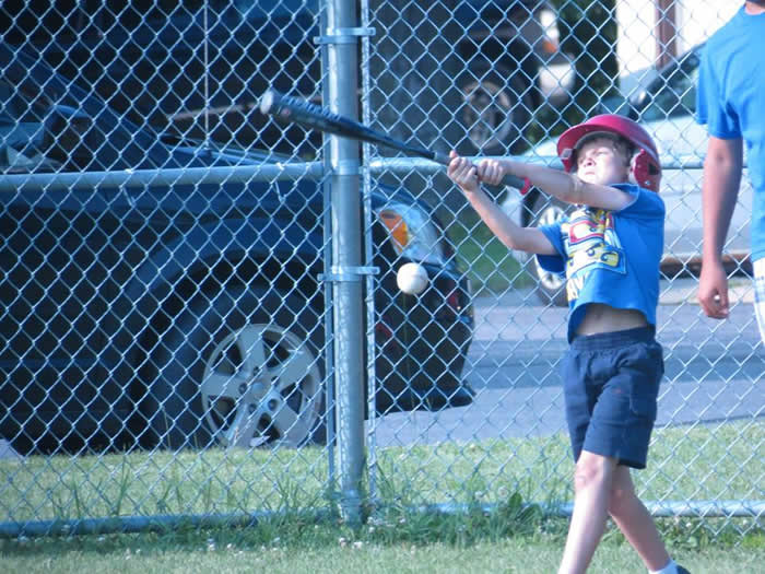 A young boy swinging a baseball bat.