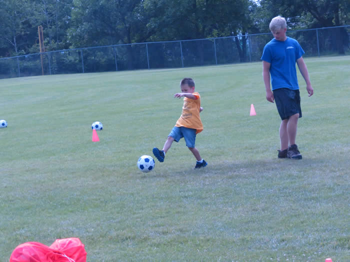 A man watching a boy practice kicking a soccer ball.