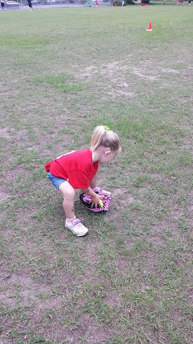 A small girl picking up a baseball from the ground.