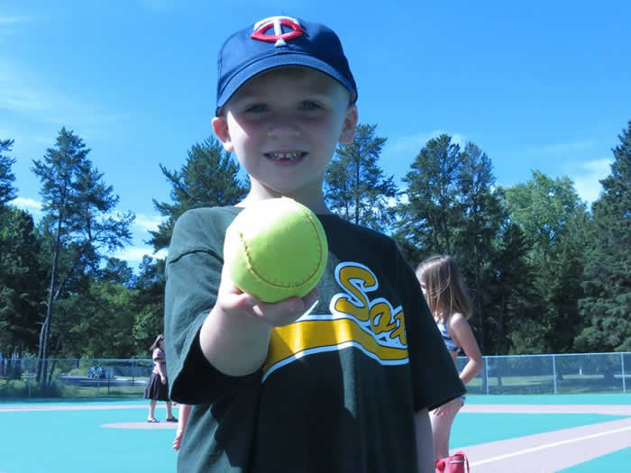A young boy holding up a softball.
