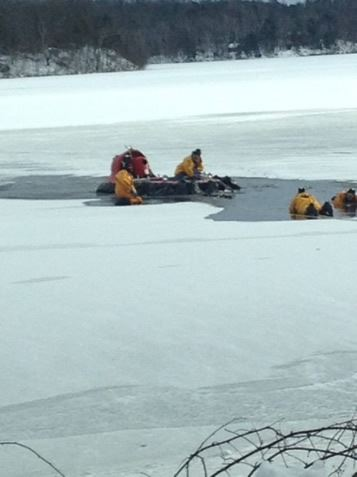 A group of firefighters retrieving a stretcher from icy water.