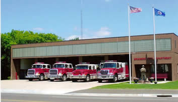 Fire engines lined up in front of the fire station on a sunny day.