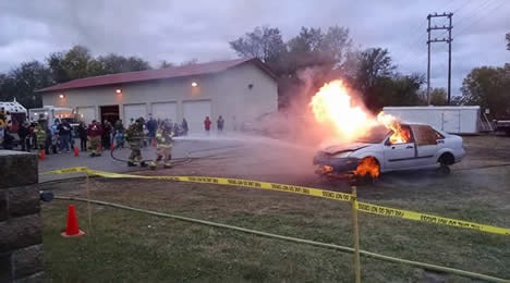 Firefighters extinguishing a car fire while a crowd watches.