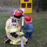 A firefighter helping a child spray a hose at a miniature house.
