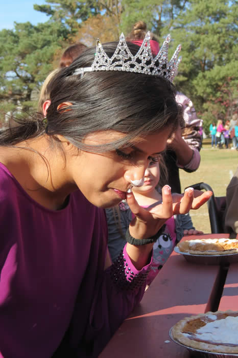 A woman in a tiara eating pie.