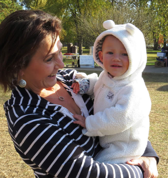 A woman holding a baby in a fuzzy white coat.