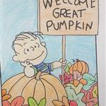 "A colored-in picture of a cartoon boy holding a sign reading, ""Welcome Great Pumpkin."""