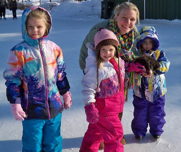A woman standing with three young girls in ice skates.