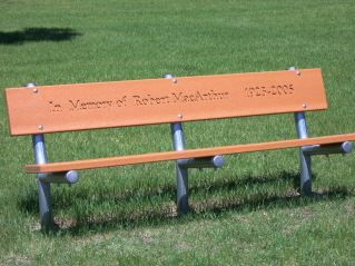 "A brown memorial bench which reads ""In Memory of Robert MacArthur, 1905 - 2005."""