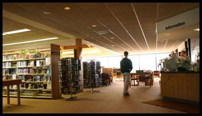 A man walking in a large library room.