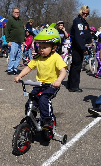 Young boy in a yellow shirt riding a bike with training wheels.
