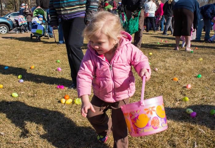 Girl in a pink coat collecting Easter eggs.