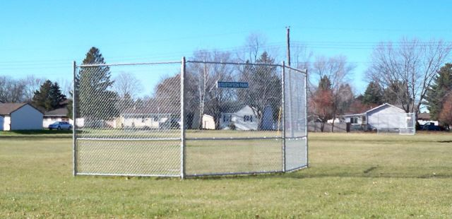 A chain-link backstop on a grassy field.