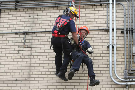 Two firefighters suspended on a rope.